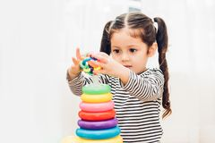 Beautiful baby girl kindergarten playing loop toy education. At interior home before preschool Royalty Free Stock Photo