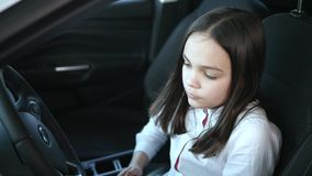 Beautiful baby girl looking away and smiling while sitting in a new car in a motor show stock video footage