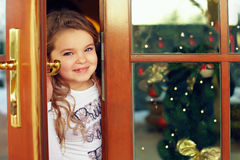 Beautiful baby girl looking out from door. Christmas portrait Royalty Free Stock Photography