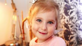 A beautiful little girl a looks at the camera and smiles. A beautiful baby girl a looks at the camera and smiles stock footage