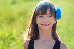 Beautiful baby girl model in summer on a background of a field with a flower on her head, royalty free stock images