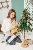 Beautiful baby girl near a Christmas tree with gifts with. Feeding black vietnamese piglet. Concept of the Chinese New Year 2019 of the Pig stock photography