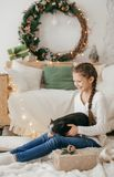 Beautiful baby girl near a Christmas tree with gifts with. Feeding black vietnamese piglet. Concept of the Chinese New Year 2019 of the Pig royalty free stock photography