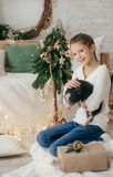 Beautiful baby girl near a Christmas tree with gifts with. Feeding black vietnamese piglet. Concept of the Chinese New Year 2019 of the Pig stock photo