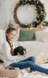 Beautiful baby girl near a Christmas tree with gifts with. Feeding black vietnamese piglet. Concept of the Chinese New Year 2019 of the Pig royalty free stock photo