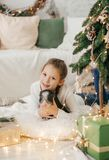 Beautiful baby girl near a Christmas tree with. Gifts with feeding black vietnamese piglet. Concept of the Chinese New Year 2019 of the Pig royalty free stock photos
