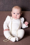 Beautiful baby girl with necklace sitting on the sofa Royalty Free Stock Photo