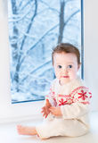 Beautiful baby girl next to window on Christmas day Stock Image