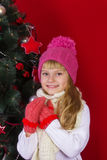 Beautiful baby girl  in a pink hat and gloves in New Year's Eve smiling and looking for a gift Stock Photos