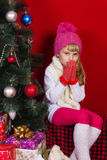 Beautiful baby girl  in a pink hat and gloves in New Year's Eve smiling and looking for a gift Royalty Free Stock Photos