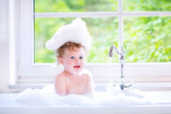 Beautiful baby girl playing with foam in big kitchen sink Royalty Free Stock Photography