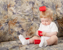Beautiful baby girl playing with hair rollers Stock Image