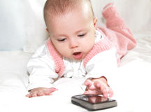 Beautiful baby girl playing with mobile Stock Images