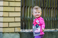 Beautiful baby girl and playing in the park among the trees and bushes near the fence Stock Photos