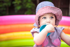 Beautiful baby girl playing in playpen with toys in the park. Cute baby girl playing in playpen with toys in the park Royalty Free Stock Images