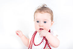 Beautiful baby girl playing with a red necklace Stock Photos
