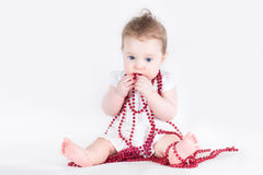 Beautiful baby girl playing with a red necklace Royalty Free Stock Images