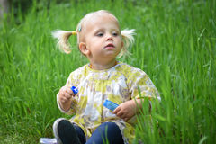 Beautiful baby girl playing with soap bubbles in the park. Royalty Free Stock Images