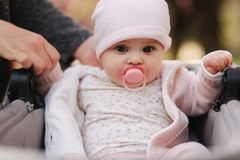 Beautiful baby girl sit in her stroller. Five month cute baby hold mom`s hands stock photos
