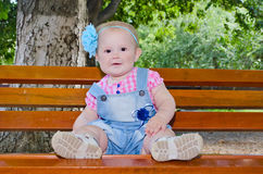 Beautiful baby girl sitting on the bench. Beautiful baby girl sitting on a bench in a park in denim overalls and a plaid shirt royalty free stock photos