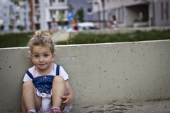 Beautiful Baby Girl Sitting on the Concrete Bench. Against the Blurred Background Royalty Free Stock Photo