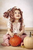 Beautiful baby girl sitting with pumpkins wearing knitted hat Royalty Free Stock Photography