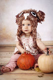 Beautiful baby girl sitting with pumpkins wearing knitted hat Stock Images