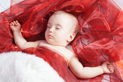 Beautiful baby girl sleeping on a red. Stock Photo