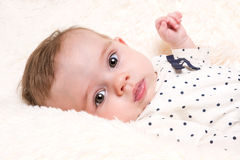 Beautiful Baby Girl in Spotty Top on Cream Fur Rug Royalty Free Stock Photography