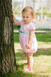 Beautiful baby girl touching a tree Royalty Free Stock Image
