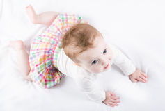Beautiful baby girl trying to crawl Stock Images