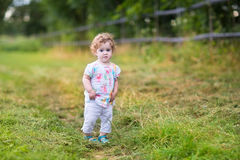 Beautiful baby girl walking on country road at sunset Royalty Free Stock Image