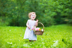 Beautiful baby girl walking with a flower basket. Beautiful baby girl walking in a sunny garden with a flower basket stock images