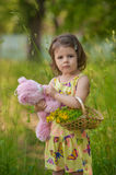 Beautiful baby girl walking in a sunny garden with a flower bask Stock Photos