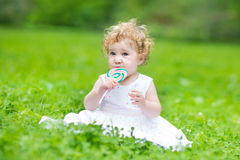 Beautiful baby girl wearing white dress eating candy in park Stock Image