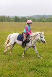 Beautiful baby girl on a white horse galloping Royalty Free Stock Image