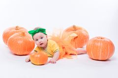 Beautiful baby girl in a yellow body with green bow on her head stock image