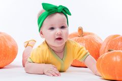 Beautiful baby girl in a yellow body with green bow on her head stock images
