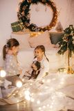 Beautiful baby girls near a Christmas tree with gifts. With little boy feeding black vietnamese piglet. Concept of the Chinese New Year 2019 of the Pig stock image