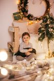 Beautiful baby girls near a Christmas tree with gifts. With little boy feeding black vietnamese piglet. Concept of the Chinese New Year 2019 of the Pig stock images