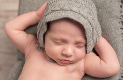 Beautiful baby in gray hat sleeping with hands behind his head Royalty Free Stock Images