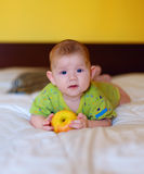 The beautiful baby holding yellow apple Royalty Free Stock Image