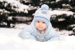 A small child in a blue overalls lying on the snow near the Christmas trees royalty free stock photography