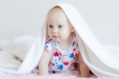 Beautiful baby kid Peeps out from under the sheets and fervently plays posing for the camera royalty free stock photo