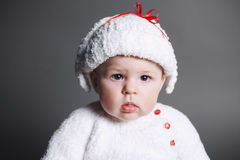 Beautiful baby in a knit dress and cap Royalty Free Stock Images