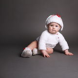Beautiful baby in a knit dress and cap Stock Photos