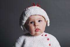 Beautiful baby in a knit dress and cap Royalty Free Stock Photography