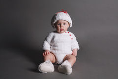 Beautiful baby in a knit dress and cap Royalty Free Stock Image