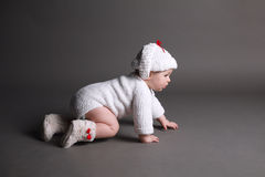 Beautiful baby in a knit dress and cap Stock Images