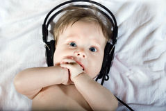 Beautiful baby listening to music royalty free stock image